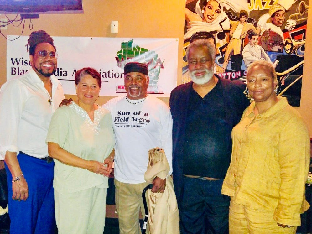 2018: Greg Stanford showed helping support the Wisconsin Black Media Association scholarship fundraiser. Also shown (left to right) reporter James E. Causey, Joanne Williams, Mikel Holt, and Liddie Collins.