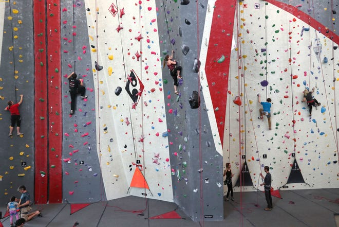People climb at Adventure Rock, 2220 N. Commerce St. The gym is among those that are participating in an upcoming fitness crawl.