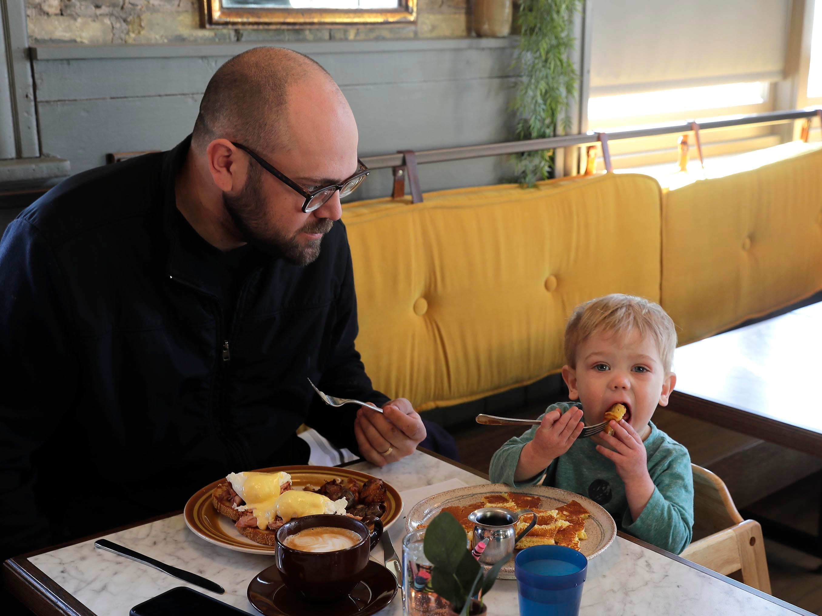 Nick Hubacher and his 18-month-old son, Wody, both from  Menomonee Falls, enjoy breakfast at  Uncle Wolfie's Breakfast Tavern.