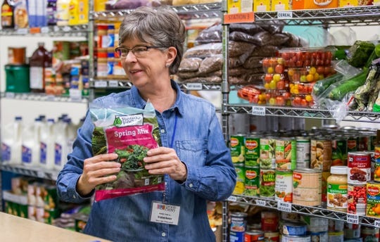 Volunteer Linda Davidson of Elm Grove assists a patron at the Food Pantry of Waukesha.