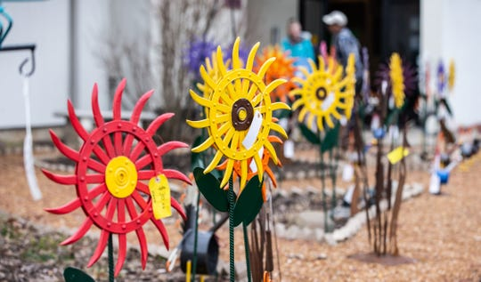Brightly colored metal yard ornaments created by artist Greg Millard of Oak Creek attract customers to the annual craft fair at All Saint's Church in Oak Creek on Saturday, April 6, 2019. Greg is retiring after years of selling his artwork at the fair.
