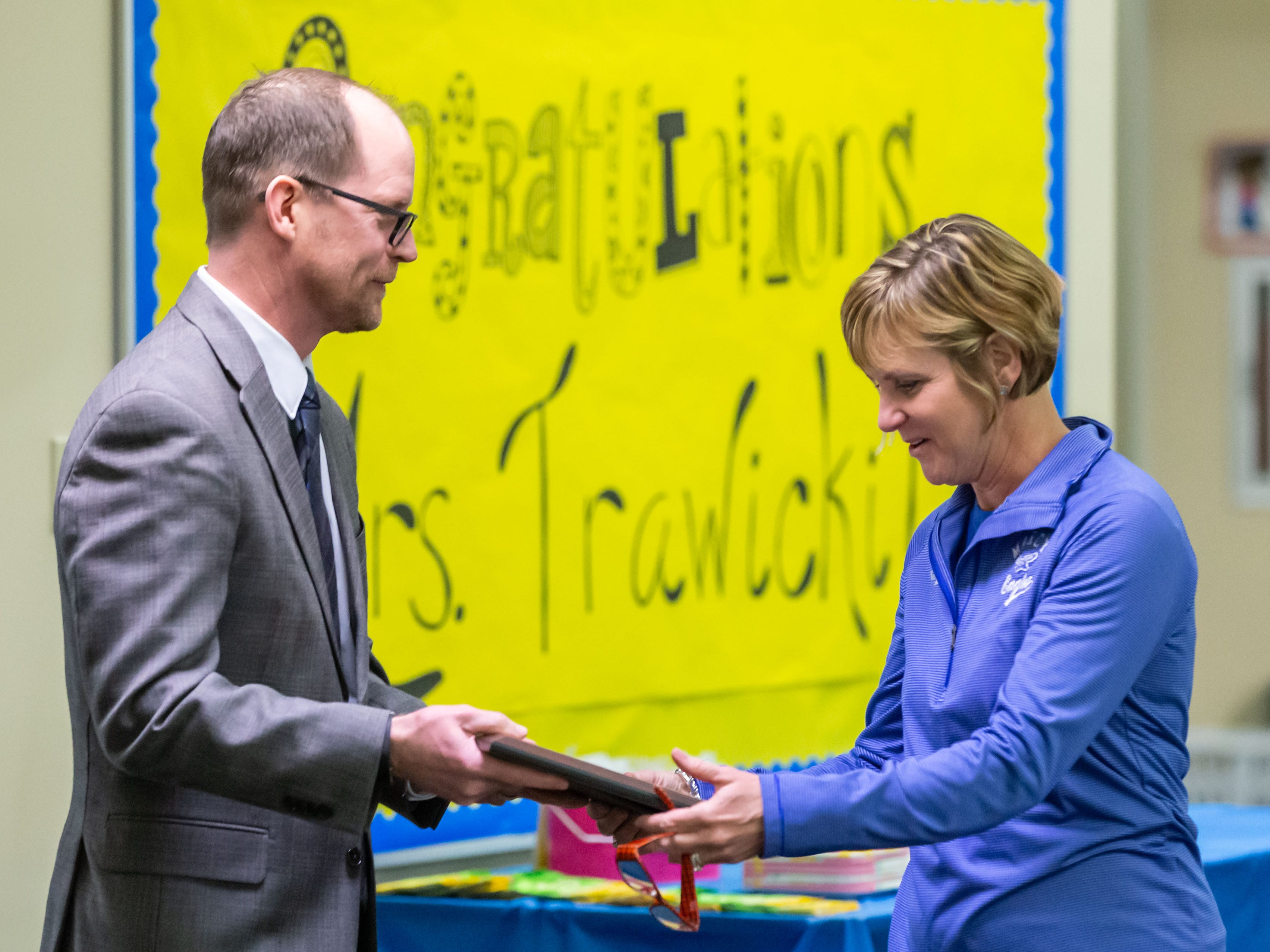 AWSA Executive Director Jim Lynch presents Marcy Elementary School Principal Michele Trawicki with a plaque after she was named the 2019 Wisconsin Elementary School Principal of the Year by the Association of Wisconsin School Administrators (AWSA) on Friday, April 5, 2019.