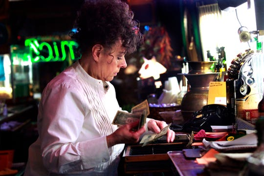 Debra Mickey makes change for a customer at Mamie's, 3300 W. National Ave. Mickey has owned the bar for nearly 38 years and it's been cash only for all that time.