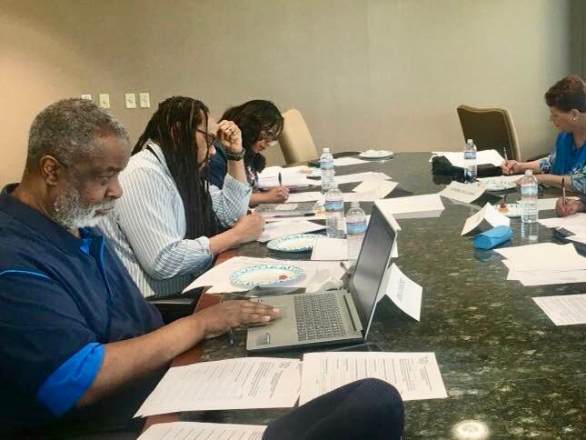 2018: Greg Stanford (left) helped to judge several scholarship contests. Last year he is shown helping to review entries from students applying for summer internships and scholarships.  Also pictured: (left to right) reporter James E. Causey; Kawanza Newsom, Joanne Williams, Vivian King, and Nathaniel Lynn.