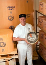 Kerry Henning holds a wheel of his peppercorn cheddar, with the plant's mammoth cheddar behind him.