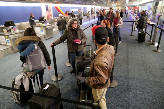 People wait in line to check their bags at the Southwest Airlines ticket area at Milwaukee Mitchell Airport late last year.