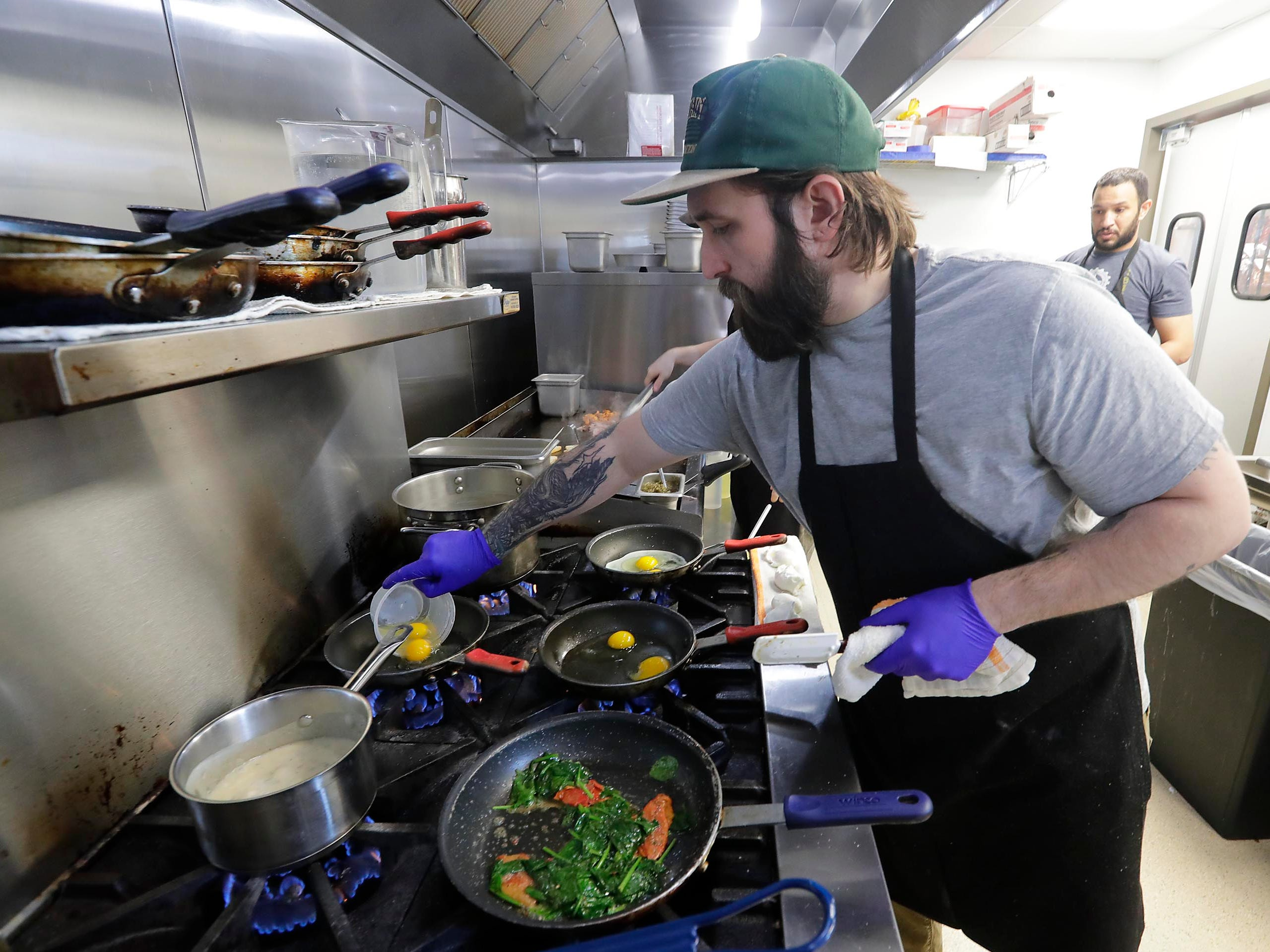 Josh Hale prepares breakfasts at  Uncle Wolfie's Breakfast Tavern, in Brewers Hill, overlooking the downtown area.