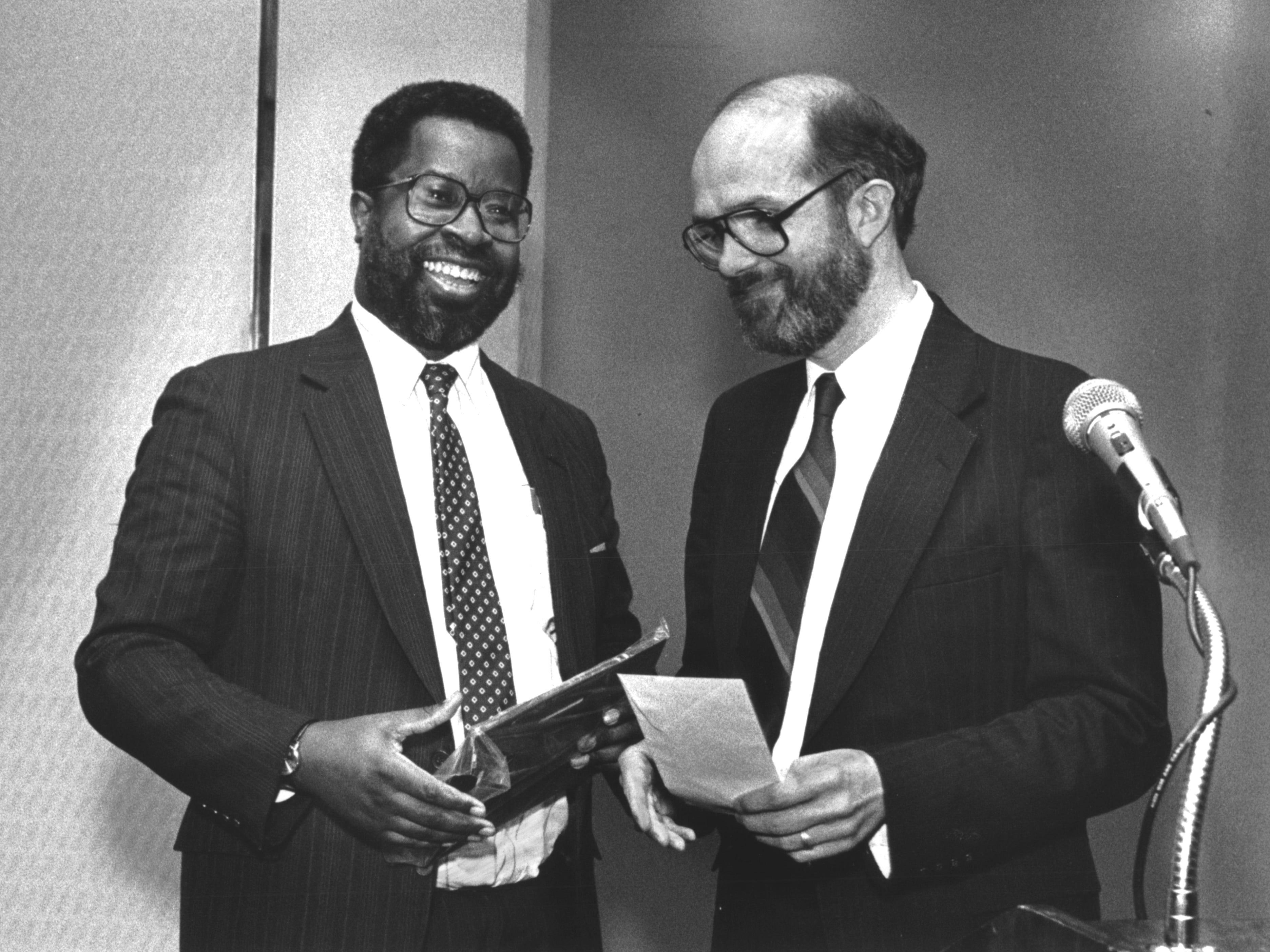 1991: Milwaukee Journal reporter Tom Heinen presents an award to Milwaukee Journal editorial writer Gregory Stanford.