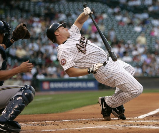 Houston Astros' Morgan Ensberg, right, falls to the ground as he avoids being hit by a pitch thrown by Milwaukee Brewers pitcher David Bush during the first inning of their Major League Baseball game Monday, April 17, 2006 in Houston. Brewers catcher Chad Moeller is left. (AP Photo/David J. Phillip)