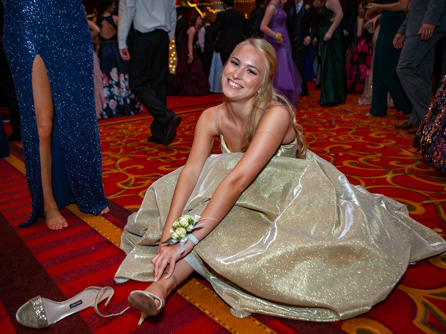 Caroline Coleman takes off her shoes at Central Magnet School's prom Saturday, April 6 at Embassy Suites in Murfreesboro.