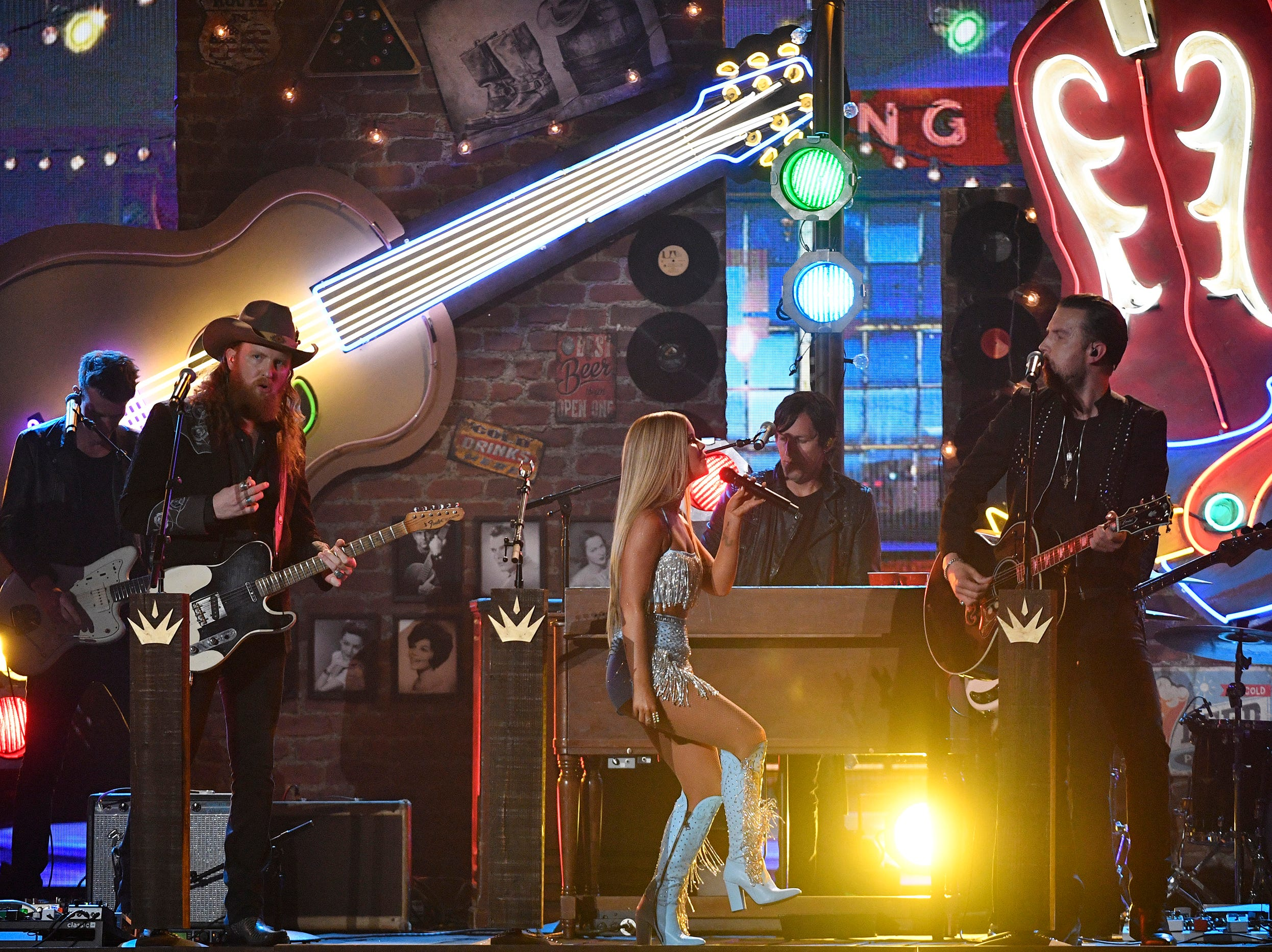 Maren Morris, center, performs with John Osborne, left, and T.J. Osborne of Brothers Osborne, during the 54TH Academy of Country Music Awards Sunday, April 7, 2019, in Las Vegas, Nev.