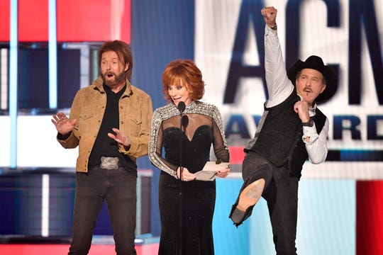 Ronnie Dunn of Brooks & Dunn, from left, host Reba McEntire, and Kix Brooks of Brooks & Dunn, react after announcing the Entertainer of The Year Award winner Keith Urban during the 54TH Academy of Country Music Awards Sunday, April 7, 2019, in Las Vegas, Nev.