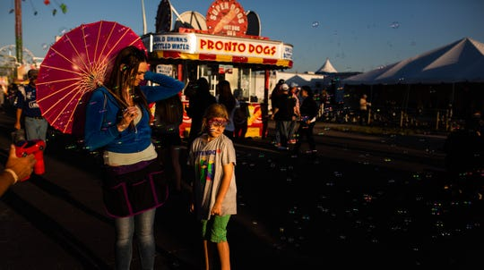Sarah Bergfjord and Samantha Mayo watch as Robert Nulder sprays bubbles at the Collier County Fair in Naples on March 22, 2019.