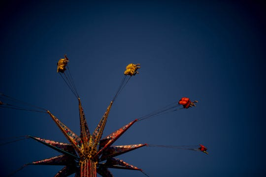 Fair-goers spin on one of the rides at the Collier County Fair in Naples on March 22, 2019.