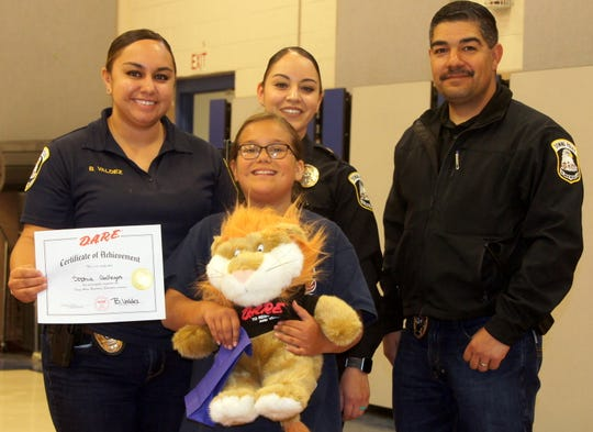 Sophia Gallegos was awarded for the top essay by, from left, Deming Police officers Britney Valdez, Ashley Ramos and assistant police chief Alex Valdespino.