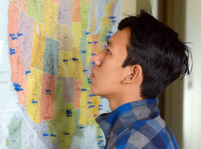 A Central American migrant at El Calvario United Methodist church studies a map showing migrant destinations.