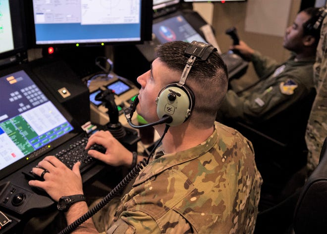 Capt. Joey (left), 6th Attack Squadron MQ-9 Reaper evaluator pilot, and Tech Sgt. Nicholas (right), 6th ATKS MQ-9 sensor operator instructor, simulate an exercise, March 13, at the 16th Training Squadron on Holloman Air Force Base, N.M. Holloman hosted 351st Special Warfare Training Squadron combat rescue officer students from Kirtland Air Force Base, N.M., March 12-14.