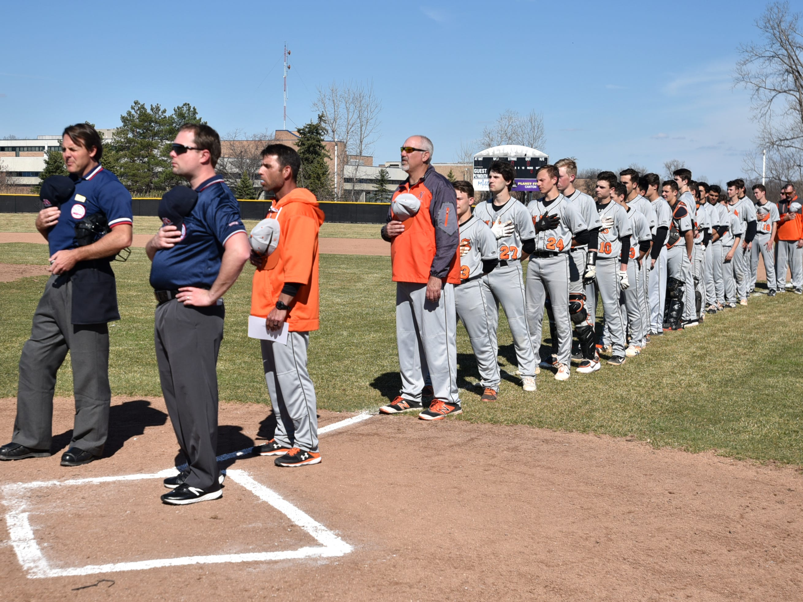 The Northville Mustangs, coaches and the game's umpires stand at attention for te playing of the National Anthem on April 8.