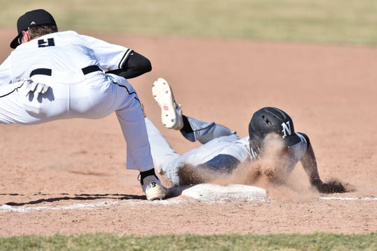 Mustang Evan Redwine eats some dust as he slides back to first ahead of a tag by Wildcat Nolen Dingledey.