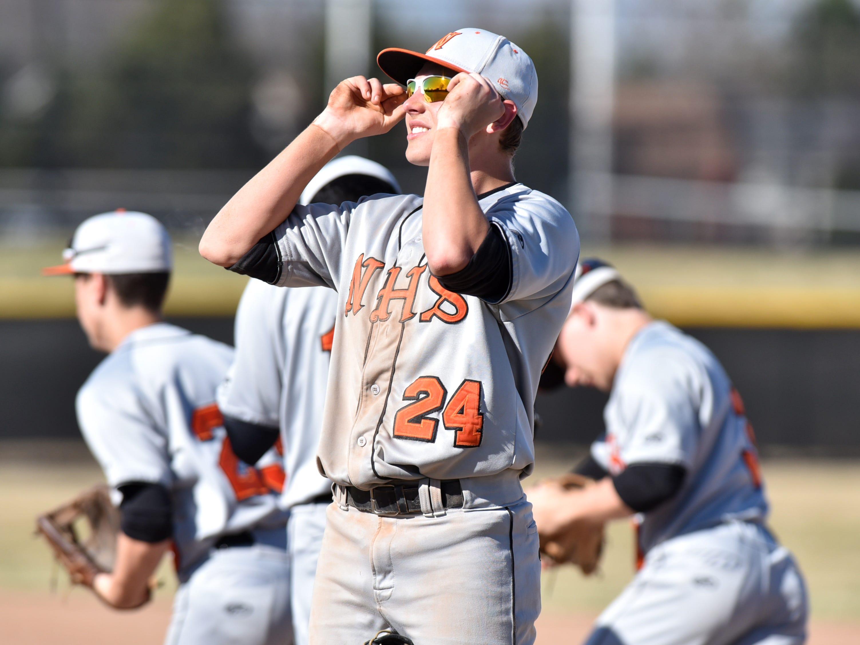 Northville Mustang Nolen Dingledey adjusts his sunglasses before beginning another inning.