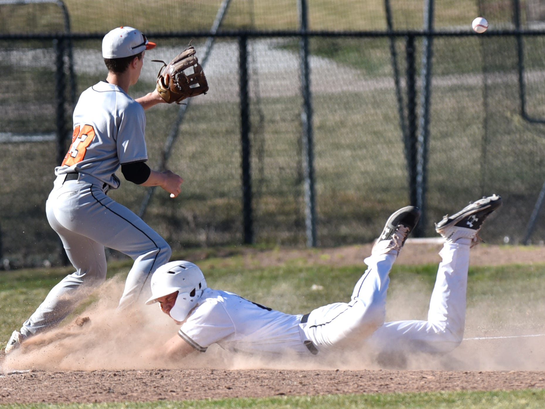 Wildcat Kai St. Germaine slides into third ahead of tag by Mustang Kameron Unger.