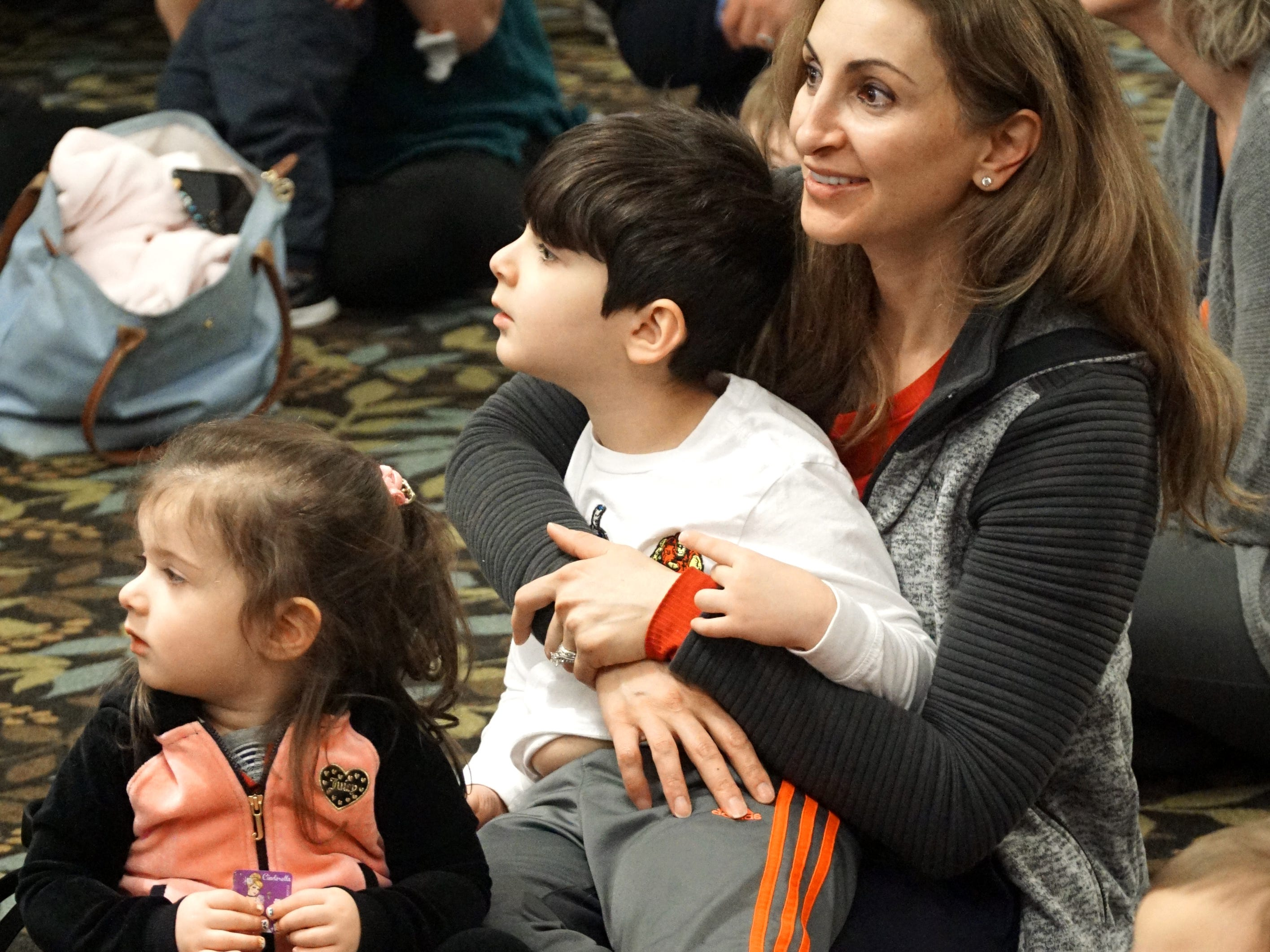 Alexandra Kief and her children Allison, 2, and Robert, 4, watch the Highland Dance routines on April 4 at the Baldwin Public Library in Birmingham.
