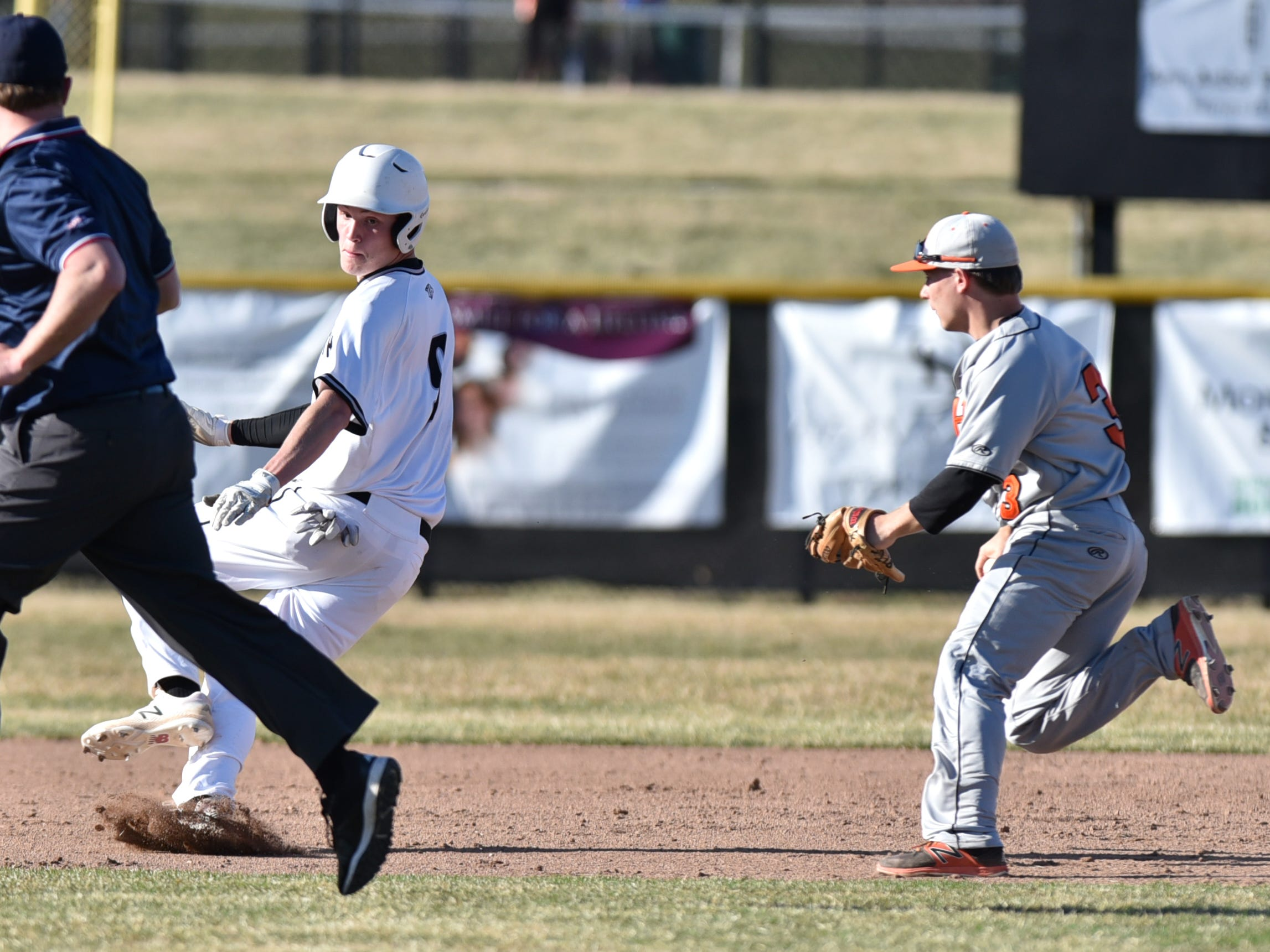 Plymouth's Anthony Sharkas, left, is caught in a run-down between second and third by Mustang Nick Prytash.