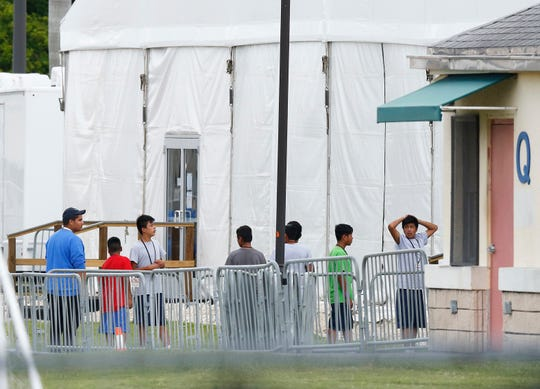 Immigrant children walk in a line June 20, 2018, outside the Homestead Temporary Shelter for Unaccompanied Children, a former Job Corps site that now houses them in Homestead, Fla.