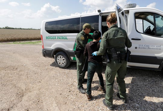 U.S. Border Patrol agents load a migrant from Guatemala into a van June 25, 2018, after he was caught trying to enter the United States illegally in Hidalgo, Texas.
