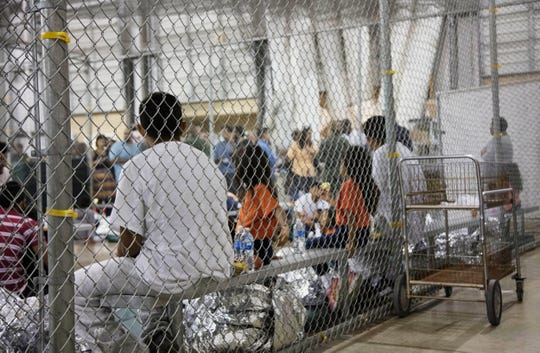 People who've been taken into custody related to cases of illegal entry into the United States, sit in one of the cages at a facility in McAllen, Texas, on June 17, 2018.