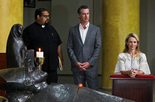 California Gov. Gavin Newsom and his wife, Jennifer Siebel Newsom, visit the tomb of Archbishop Oscar Romero at Metropolitan Cathedral in San Salvador, El Salvador, on Sunday, April 7, 2019. Father Francisco Villalobos stands at left.