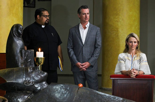 California Gov. Gavin Newsom and his wife, Jennifer Siebel Newsom, visit the tomb of Archbishop Oscar Romero at Metropolitan Cathedral in San Salvador, El Salvador, on Sunday, April 7, 2019. Father Francisco Villalobos stands at left.