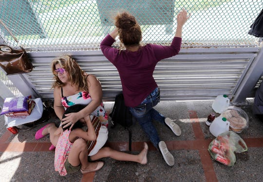 Immigrants from Honduras seeking asylum wait June 24, 2019, on the Gateway International Bridge, which connects the United States and Mexico, in Matamoros, Mexico.