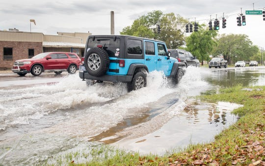 Vehicles on Monday drive through a section of flooded road on Barrancas Avenue near its intersection with West Government Street in Pensacola.