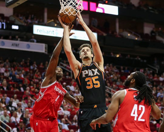 Apr 7, 2019; Houston, TX, USA; Phoenix Suns forward Dragan Bender (35) shoots the ball against Houston Rockets forward Danuel House Jr. (4) and center Nene Hilario (42) during the third quarter at Toyota Center. Mandatory Credit: Troy Taormina-USA TODAY Sports