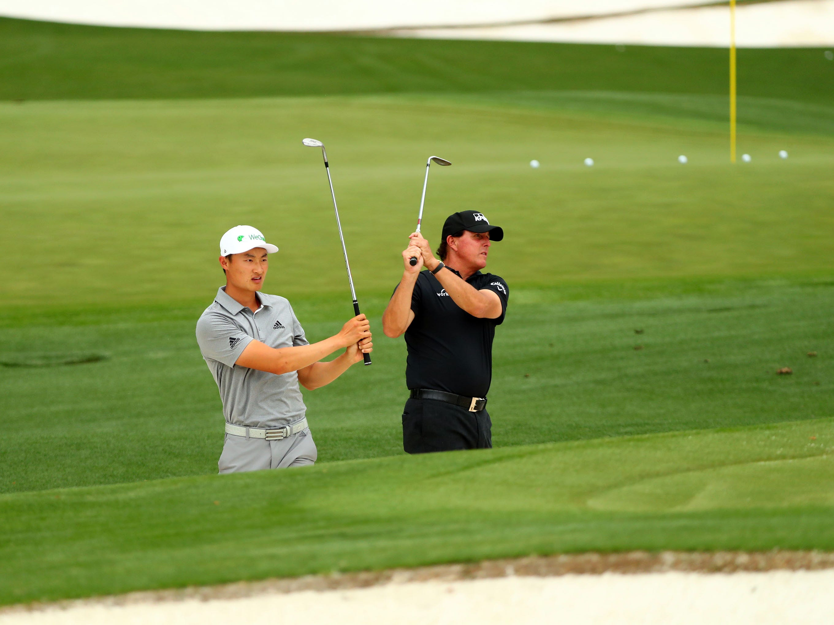 Apr 8, 2019; Augusta, GA, USA; Haotong Li of China and Masters champion Phil Mickelson (right) blast from a bunker on the practice facility during a practice round for the Masters golf tournament at Augusta National Golf Club.