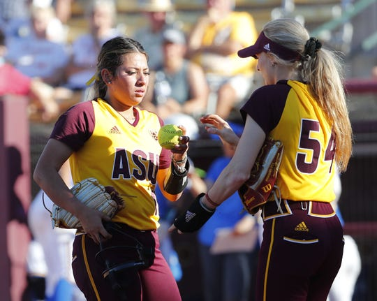 ASU pitcher Samantha Mejia (left) gives the ball up to pitcher Abby Andersen during the second inning against UCLA at Farrington Stadium in Tempe, Ariz. April 7, 2019.