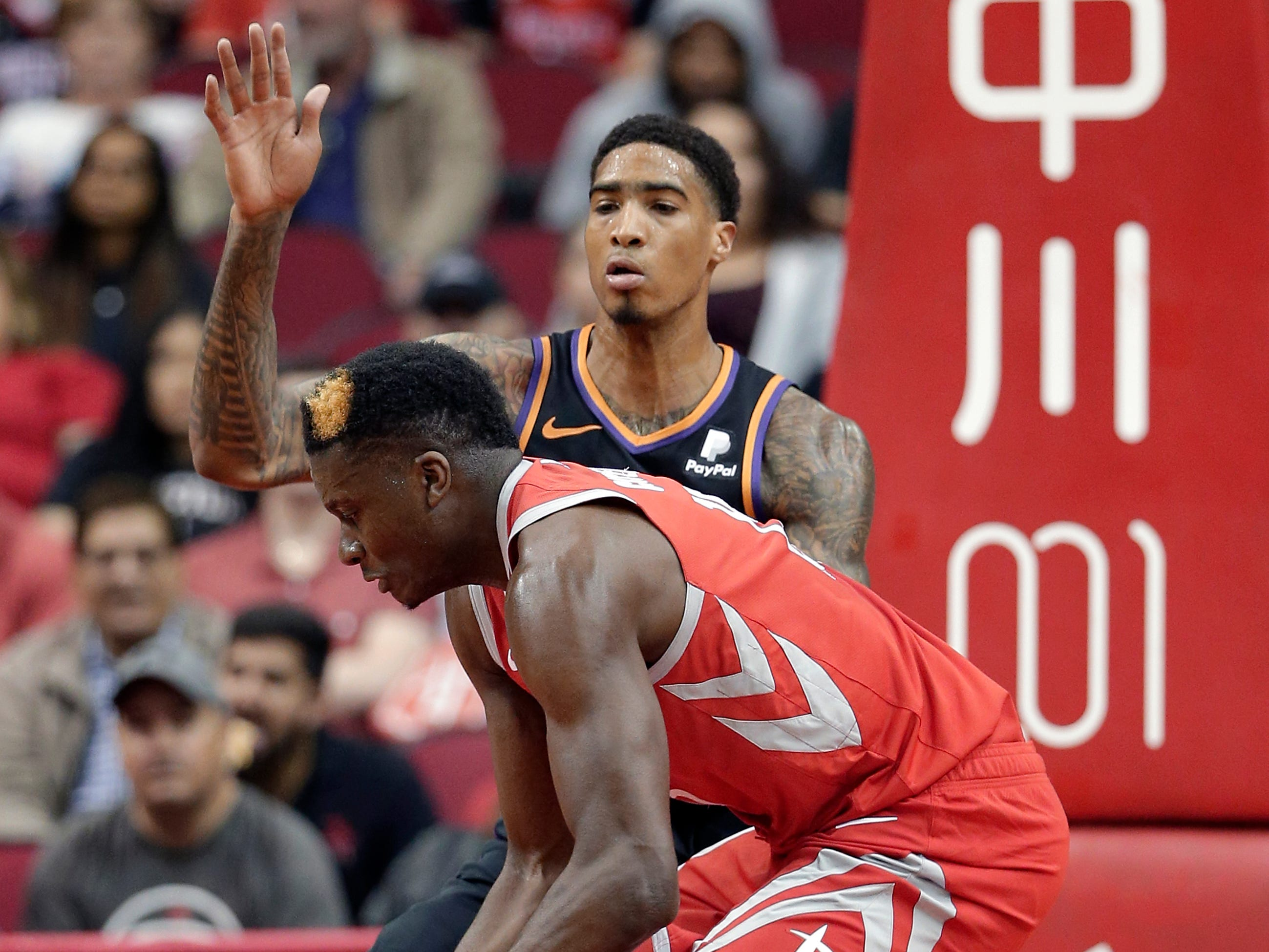 Houston Rockets center Clint Capela, front, recovers a rebound after is was knocked away by Phoenix Suns forward Ray Spalding, back, during the first half of an NBA basketball game Sunday, April 7, 2019, in Houston. (AP Photo/Michael Wyke)