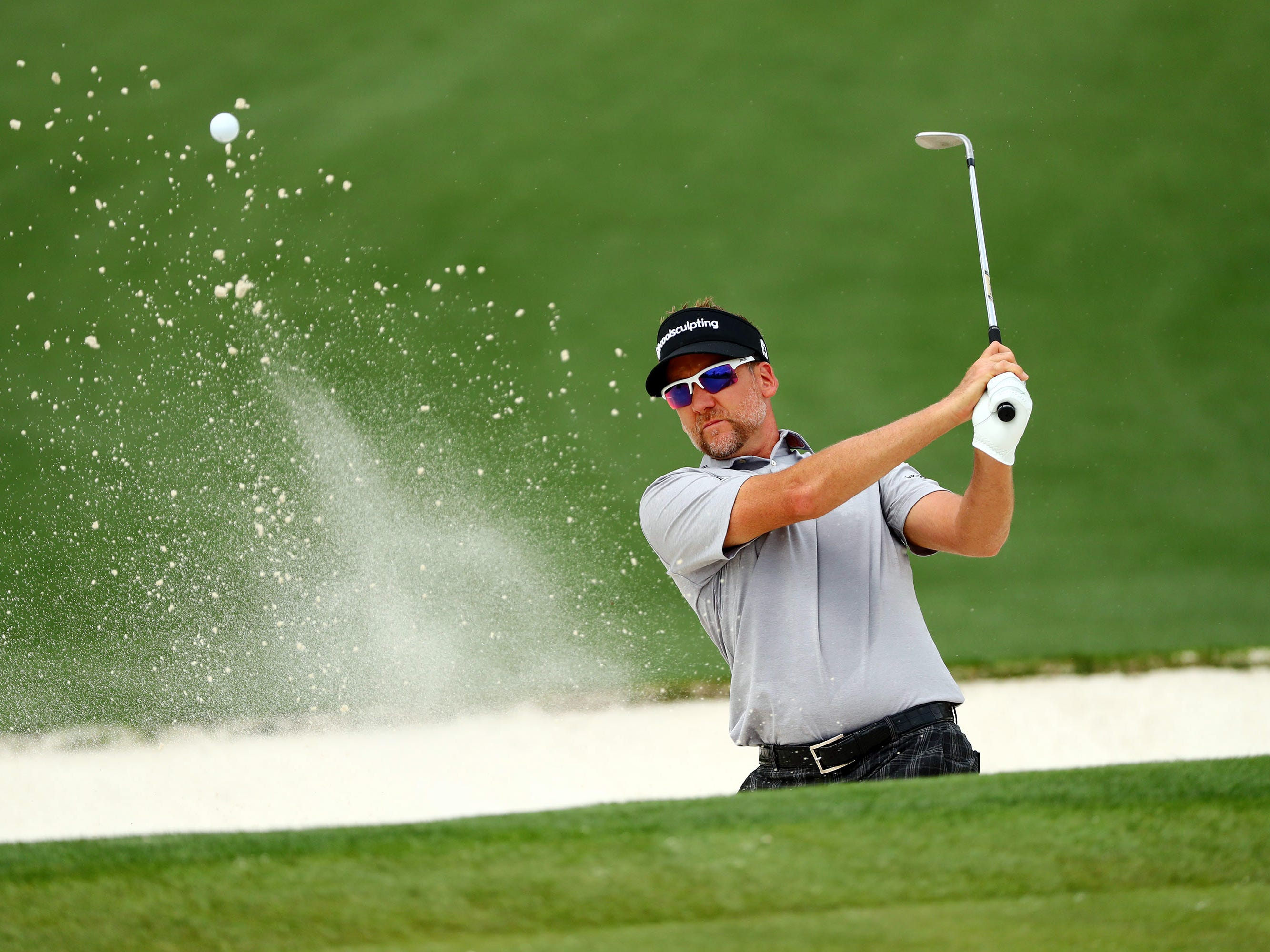 Apr 8, 2019; Augusta, GA, USA; Ian Poulter of England blasts out a green side bunker on the second hole during a practice round for the Masters golf tournament at Augusta National Golf Club.
