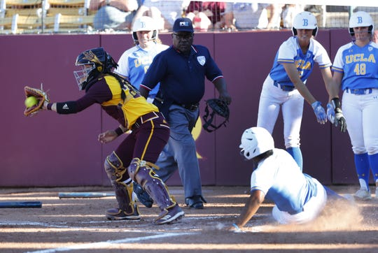 UCLA's Aaliyah Jordan scores ahead of the throw fielded by ASU catcher Maddi Hackbarth during the second inning at Farrington Stadium in Tempe, Ariz. April 7, 2019.