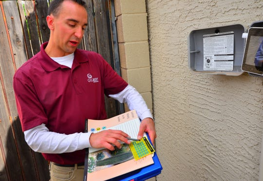 Gilbert water conservation technician Andrew Pirrone explains irrigation timing during a water audit on April 4, 2019.
