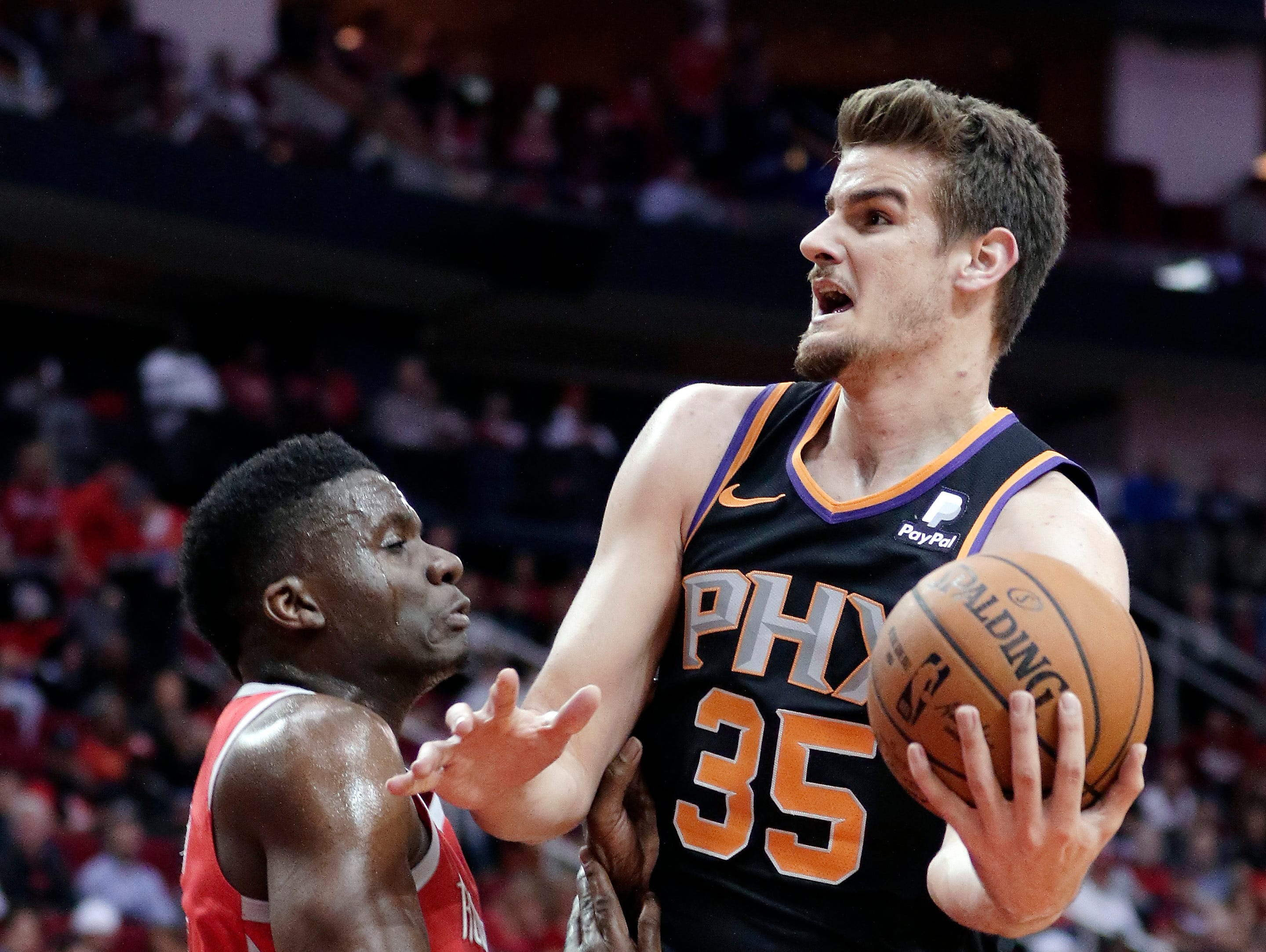 Phoenix Suns forward Dragan Bender (35) drives to shoot over Houston Rockets center Clint Capela, left, during the first half of an NBA basketball game Sunday, April 7, 2019, in Houston. (AP Photo/Michael Wyke)