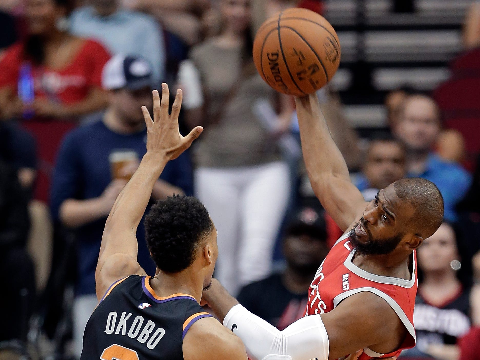 Houston Rockets guard Chris Paul, right, passes the ball over Phoenix Suns guard Elie Okobo (2) during the first half of an NBA basketball game Sunday, April 7, 2019, in Houston. (AP Photo/Michael Wyke)