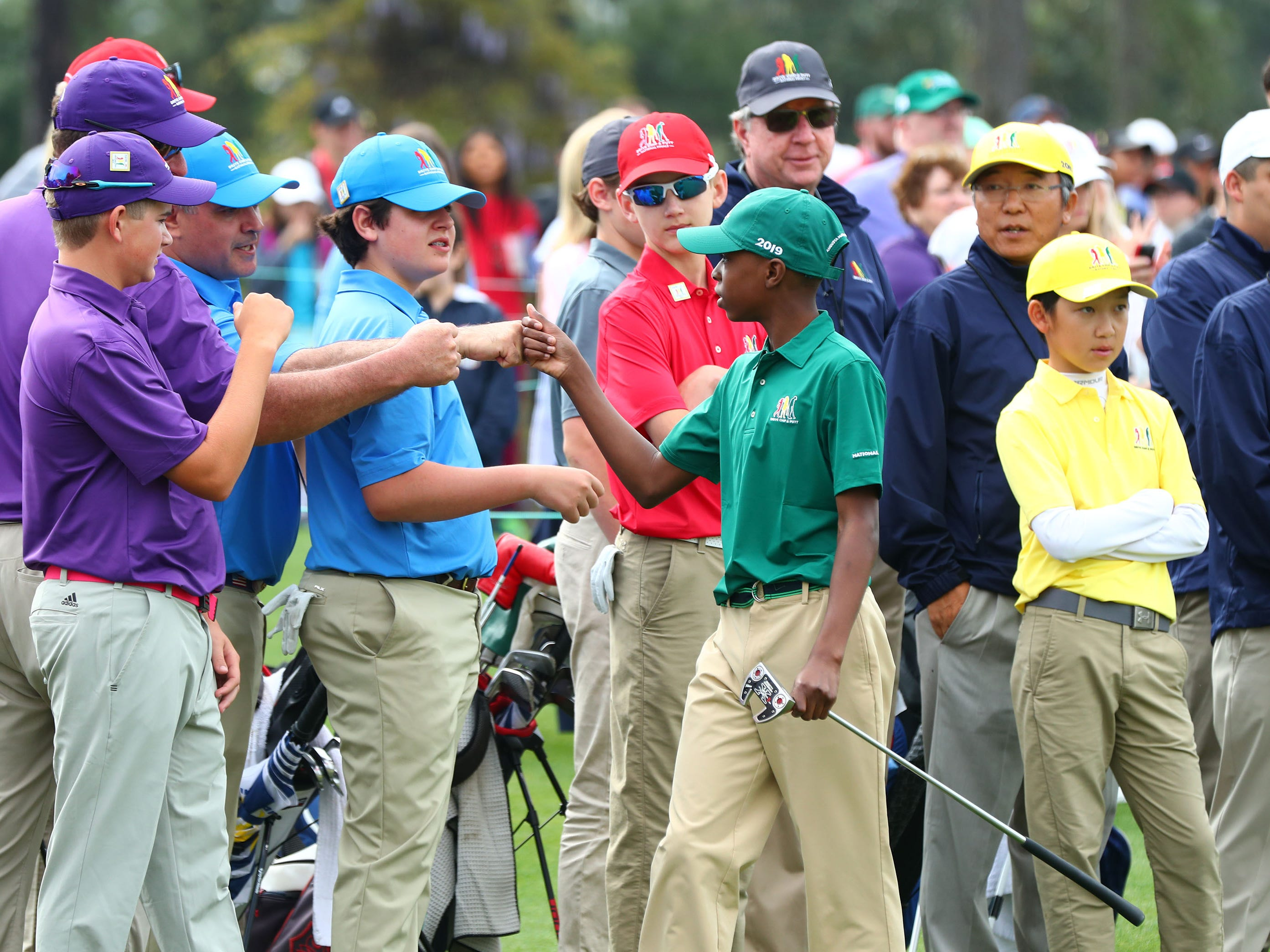 Apr 7, 2019; Augusta, GA, USA; Overall championÊMatthew Vital of Bethlehem, PA.Ê(green cap) for the boys 11-12 age group, bumps fists with after putting during the finals of the Drive, Chip and Putt competition at Augusta National Golf Club. Mandatory Credit: Rob Schumacher-USA TODAY Sports