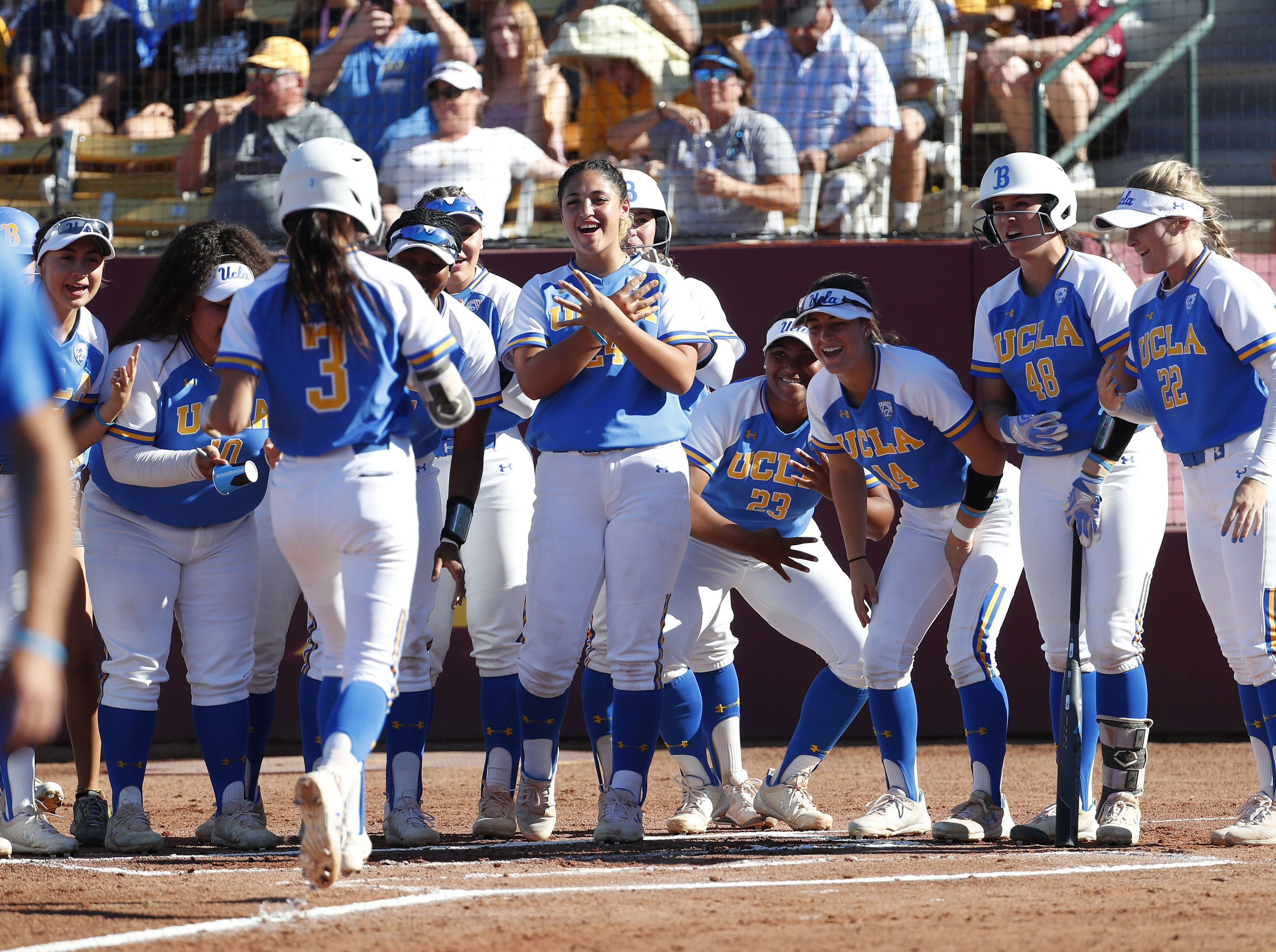 UCLA's Briana Perez is greeted at home after her solo home run against ASU during the first inning at Farrington Stadium in Tempe, Ariz. April 7, 2019.