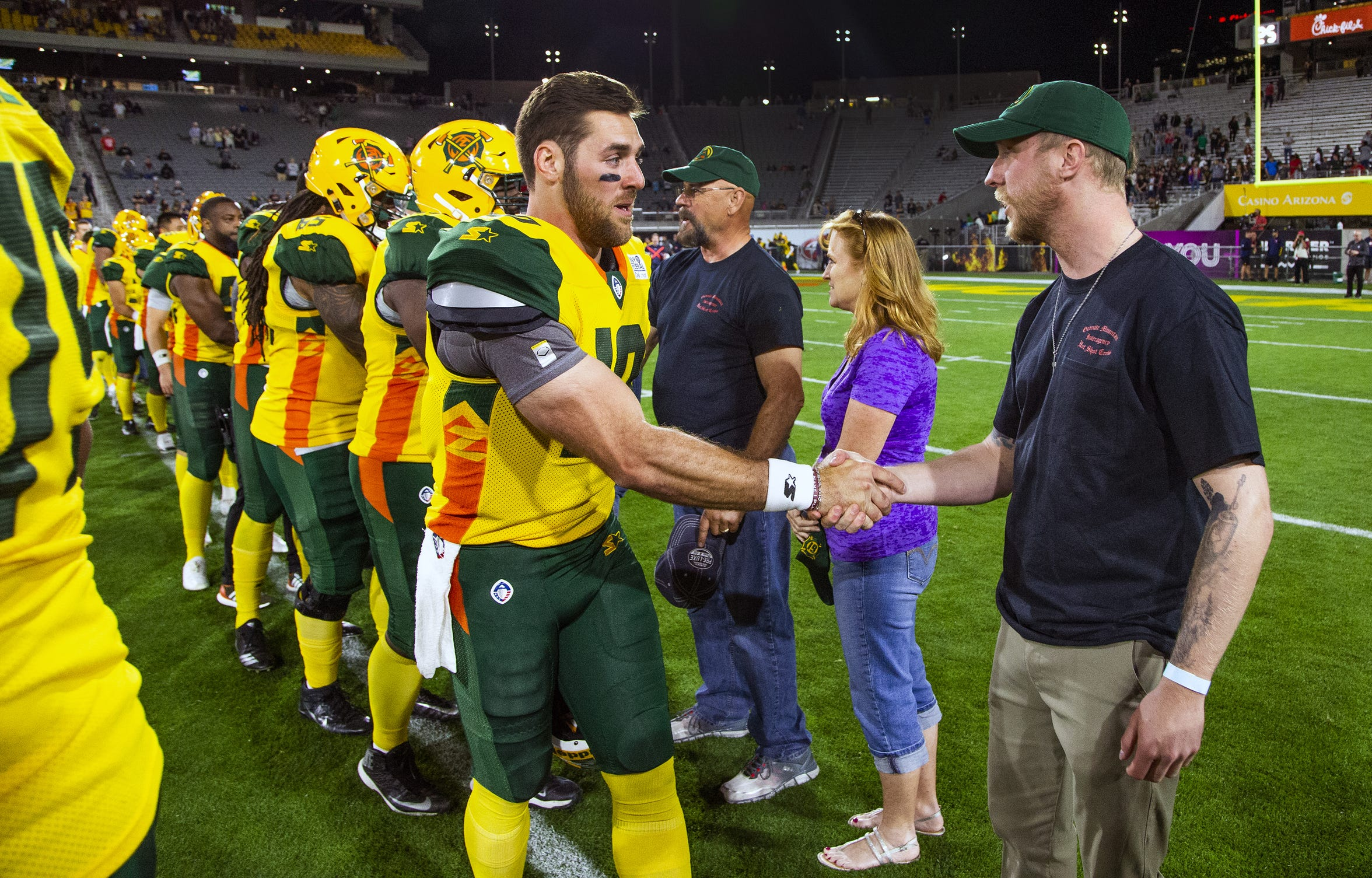 Brendan McDonough, the lone-surviving member of the Granite Mountain Hotshots, greets quarterback Trevor Knight and other members of the Arizona Hotshots after being honored along with family members of the crew at a game last month.