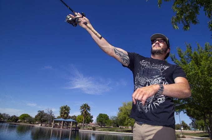 Kyle Cohen, 37, casts his line in the pond at Desert Breeze Park in Chandler on Monday, April 8, 2019. Temperatures in the 90's made a nice day for fishing.
