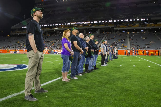 Brendan McDonough, the lone-surviving member of the Granite Mountain Hotshots, and family members of the crew watch a tribute while being honored at the Arizona Hotshots' game on March 3.