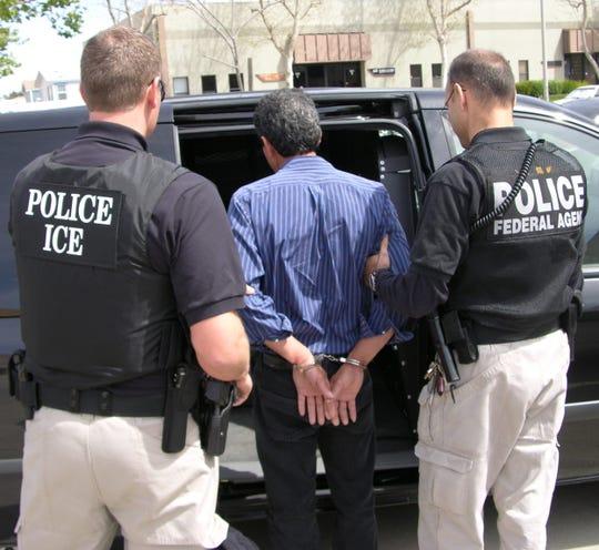 Agentes del ICE arrestan a una persona.