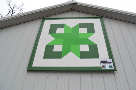 """This barn quilt, called """"Stars in the Attic,"""" hangs on a barn at the Ottawa County Fairgrounds. It was painted by the Ottawa County 4-H Jr. Leadership Club. Installed on June 24, 2017, it was the first barn quilt created for the Ottawa County Barn Quilt Trail."""